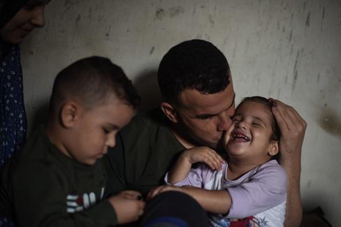 Le pêcheur Khader al-Saidi joue avec ses enfants. « Israël a détruit ma vie. Je suis encore jeune, mais j'ai perdu tout ce qui me rendait heureux : la mer et pouvoir voir mes enfants et sentir leur odeur », dit-il. (Photo : Abed Zagout / The Electronic Intifada)