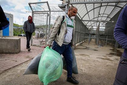 Des travailleurs palestiniens venus de la ville de Hébron (Cisjordanie) transportent leurs affaires personnelles quand ils arrivent au check-point de Tarqumiya pour se rendre en Israël. (Photo : Wisam Hashlamoun/Flash90)