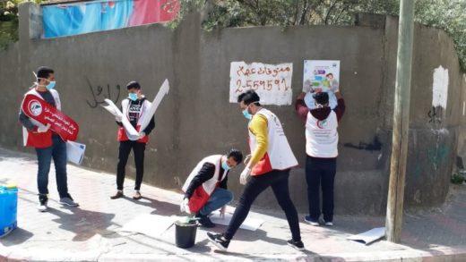 Gaza : Des jeunes collent des consignes concernant la Covid pour la population