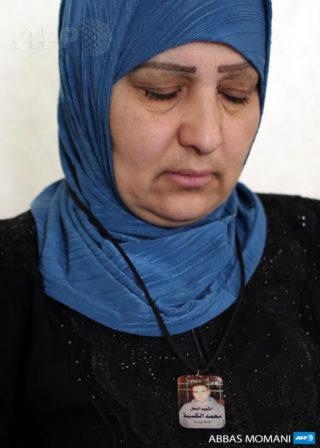 13 juillet 2015. Assise dans sa maison du camp de réfugiés de Qalandia, Umm Thaer, la mère de Yasser, de Samer et de Mohammad Kasba, porte un collier avec la photo de Mohammad. (Photo : AFP / Abbas Momani)