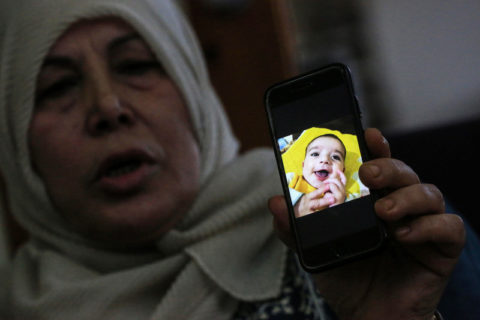23 juin 2020. La grand-mère d'Omar Yaghi montre une photo de l'enfant de 9 mois, plusieurs jours après son décès d'une insuffisance cardiaque, alors que ses parents attendaient un permis israélien pour sortir de Gaza en vue d'un traitement médical destiné à lui sauver la vie. (Photo : Ashraf Amra APA images)