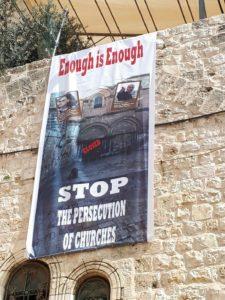 """Une banderole sur la façade de l'église du Saint Sépulcre à Jérusalem : """"Assez c'est assez – Stop aux persécutions contre les églises"""""""