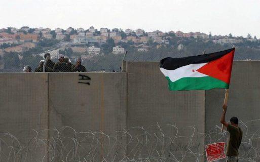Septembre 2011. Au cours d'une manifestation à Bil'in, un protestataire palestinien brandit un drapeau à proximité du mur israélien de l'apartheid/annexion. (Photo: Issam Rimawi/Flash90)