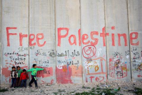 3 avril 2014. Des enfants palestiniens rassemblés au pied de la barrière israélienne de séparation, dans le village d'Abu Dis, à Jérusalem-Est. (Photo : Saeed Qaq/APA Images)