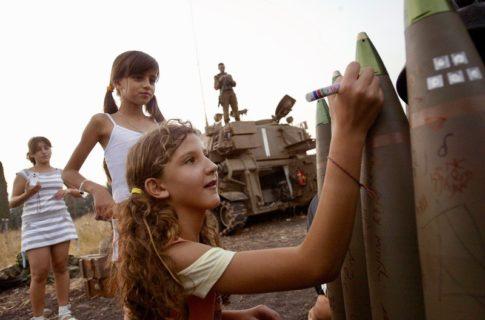 17 juillet 2006. De jeunes Israéliennes de Kiryat Shmona, dans le nord d'Israël, écrivent des messages sur de lourds obus d'artillerie avant qu'ils ne soient tirés vers le Liban. L'offensive israélienne de cet été-là visait les civils et les infrastructures, causant des morts et des destructions en masse.