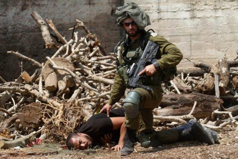 23 août 2019. Un soldat israélien s'accroupit au-dessus d'un manifestant palestinien dans le village de Kfar Qaddum, près de Naplouse. (Photo : Nasser Ishtayeh/Flash90)
