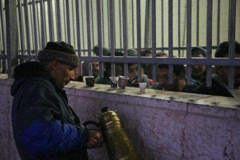 8 février 2017, Bethléem, Cisqjordanie. Un Palestinien vend du café à des travailleurs palestiniens attendant à un check-point de pouvoir se rendre à leur travail. (Photo : Activestills.org)
