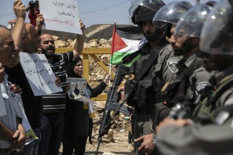 12 août 2016. À Nabi Saleh, un village de Cisjordanie. Des manifestants palestiniens brandissent des drapeaux alors qu'ils discutent avec des hommes de la police israélienne des frontières au cours d'une manifestation de solidarité avec les prisonniers palestiniens détenus dans les geôles israéliennes. (Photo : Flash90)