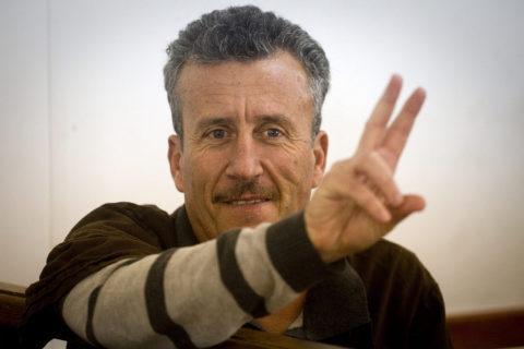 Bassem Tamimi fait un signe de paix lors de son procès devant un tribunal militaire israélien. (Photo : Oren Ziv)