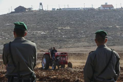 19 novembre 2013, village de Kustra, Cisjordanie. Des agents de la police israélienne des frontières montent la garde pendant que des fermiers palestiniens utilisent leurs tracteurs pour travailler les terres de leur village. (Photo : Nati Shohat / Flash90)