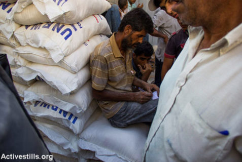 Les Gazaouis reçoivent des rations alimentaires de l'UNRWA lors d'un cessez-le-feu, à Gaza, le 17 août 2014. Chaque famille reçoit un sac de farine et un autre sac de riz. Photo : Anne Paq/Activestills