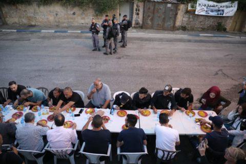 7 mai 2021. Des Palestiniens organisent leur repas nocturne de l'Iftqar, qui rompt le jeûne du Ramadan, à l'extérieur d'une maison palestinienne précédemment reprise par des colons israéliens dans le quartier de Sheikh Jarrah, à Jérusalem-Est. L'Iftar faisait partie d'une veille nocturne organisée dans le quartier par les Palestiniens pour protester contre l'expulsion prévue de quatre autres familles palestiniennes de leurs maisons dans le quartier. (Photo : Oren Ziv)