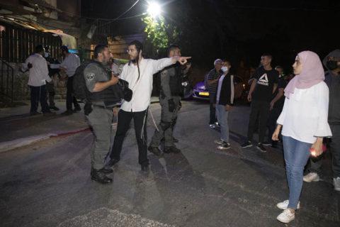 4 mai 2021. Muna El-Kurd (à droite) observe un colon israélien qui parle à un policier au cours d'une veille contre l'expulsion imminente de plusieurs familles palestiniennes du quartier de Sheikh Jarrah, à Jérusalem-Est. (Photo : Oren Ziv)