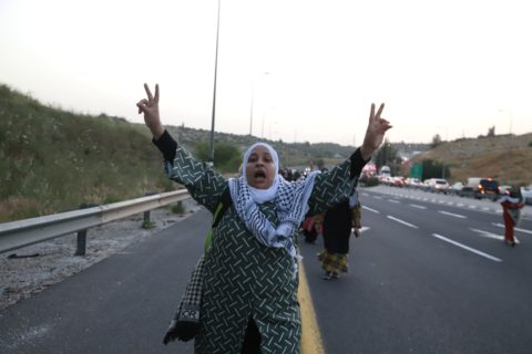 8 mai 2021. Une Palestinienne à pied sur la Route 443 en Cisjordanie. Elle se rend à Jérusalem pour les prières du ramadan après que la police israélienne a bloqué le trafic vers la ville afin d'empêcher plus de Palestiniens encore d'y entrer. (Photo : Oren Ziv)