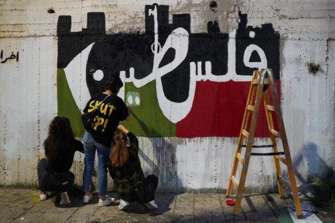 Au cours de la grève générale du 18 mai 2021, des citoyens palestiniens d'Israël peignent sur un mur de Nazareth le mot « Palestine » en arabe. (Photo : Maria Zreik / Activestills)
