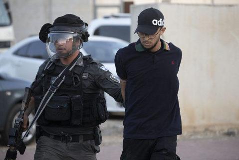 Un policier israélien arrête un Palestinien dans la ville de Lydd, dans le centre d'Israël. (Photo: Oren Ziv)