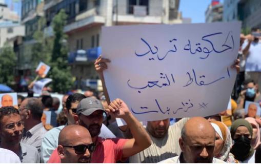 24 juin 2021. Après la mort de Nizar Banat, un manifestant à Ramallah brandit une pancarte disant « Le régime veut la chute du peuple ». (Photo : MEE / Shatha Hammad)
