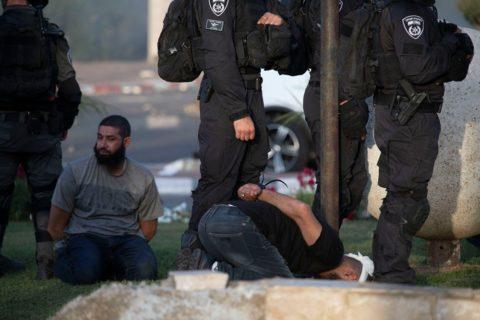 Des policiers israéliens ceignent d'un bandeau la tête d'un citoyen palestinien d'Israël au moment des manifestations de protestation à Lydd, dans le centre d'Israël. (Photo: Oren Ziv)