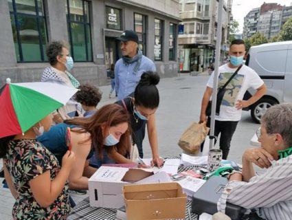 Des passantes écrivent des cartes de soutien à Khalida Jarrar, au stand Palestine. Photo : Plate-forme Charleroi-Palestine (MDL)