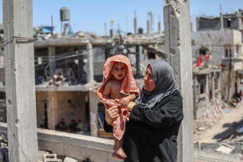 Une femme donne son bain à un enfant à proximité des ruines de leur habitation, détruite par une frappe aérienne israélienne dans le nord de la bande de Gaza. (Photo : Mohammed Zaanoun / ActiveStills)