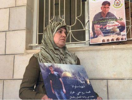 Fatima Hammad tient une affiche représentant son fils dans la ville cisjordanienne occupée de Silwad. (Photo : MEE / Shatha Hammad)