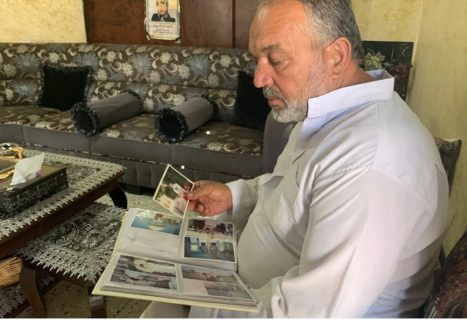 Khaled Afana regarde des photos de sa fille Maï, dans la maison familiale d'Abou Dis, près de Jérusalem. (Photo : MEE / Shatha Hammad)