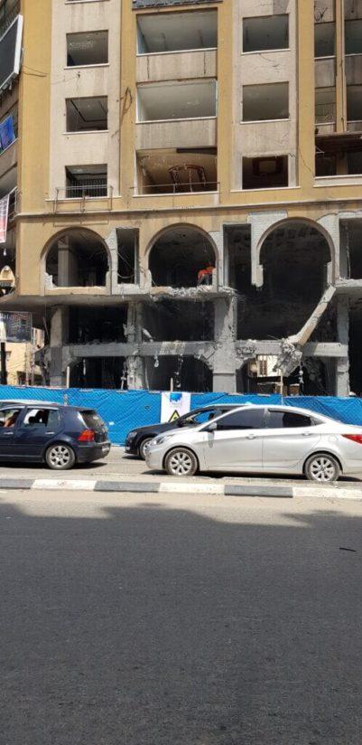 La tour commerciale d'Al-Jawhra. Elle a été frappée à trois reprises par les avions de combat mais, du fait qu'elle est très large, elle ne s'est pas effondrée. Remarquez comment la bombe a visé les fondations. On peut voir des ingénieurs égyptiens qui regardent s'il est possible de la reconstruire. (Photo : Emad Moussa, juin 2021)