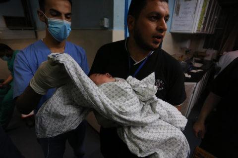 """Une infirmière tient un bébé rescapé des frappes aériennes d'Israël le 15 mai contre le camp de réfugiés """"Beach Camp"""", à Gaza.(Photo: Ashraf Amra / APA images)"""